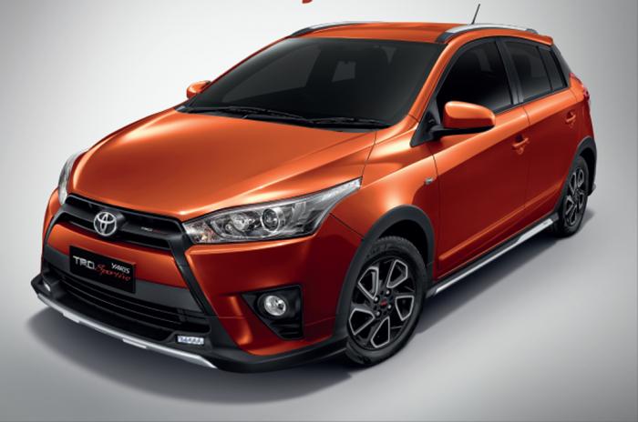 gambar menunjukkan sebuah mobil Toyota Yaris berwarna orange sedang diparkir di pinggir jalan
