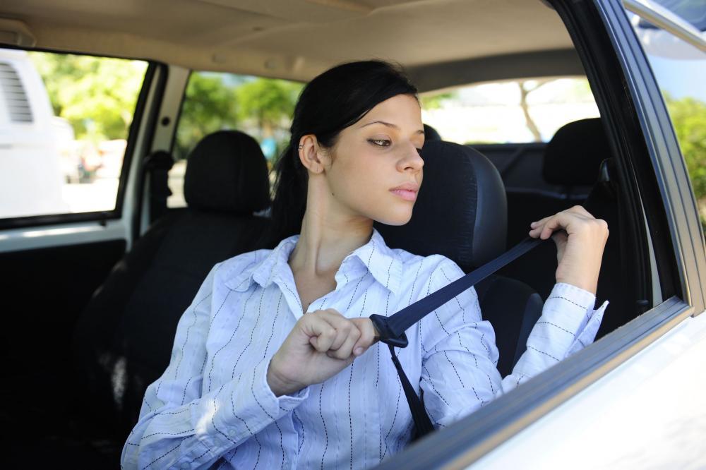 gambar menunjukkan seorang wanita sedang menggunakan seatbelt sebelum mengemudi