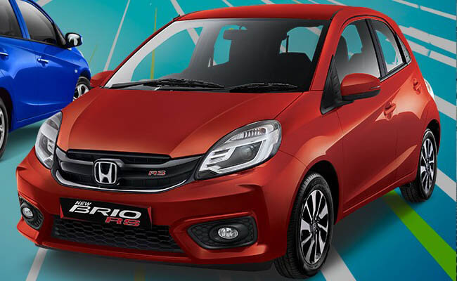 gambar menunjukkan sebuah mobil Honda Brio Satya E 2014 berwarna merah sedang diparkir di pinggir jalan