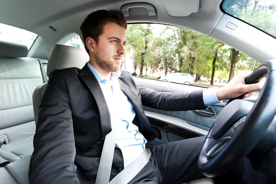 gambar menunjukkan seorang pria sedang memakai sabuk pengaman sebelum mengemudi