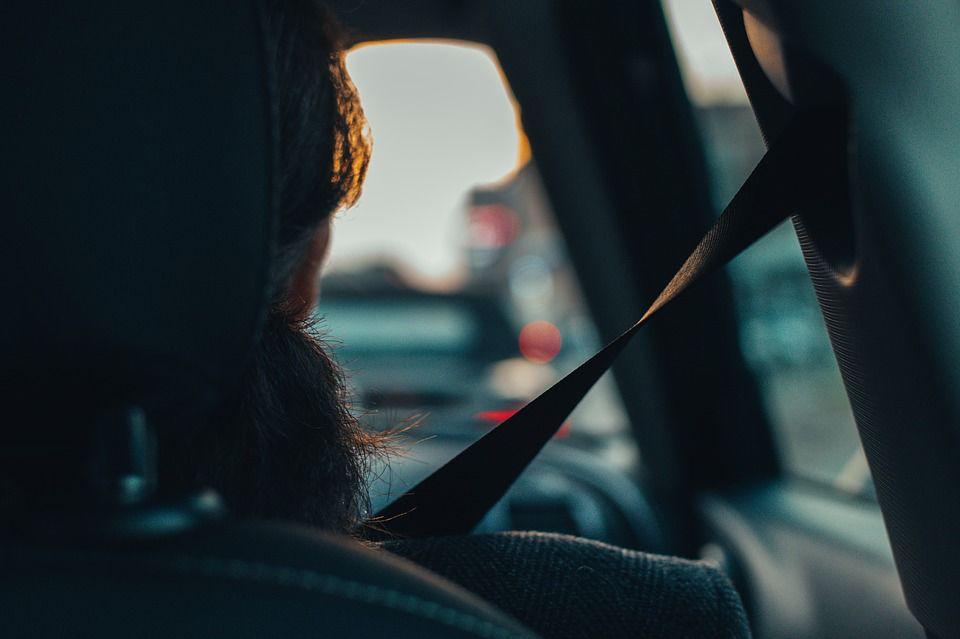 gambar menunjukkan seorang pria dilihat dari belakang jika sedang mengemudi di jalan