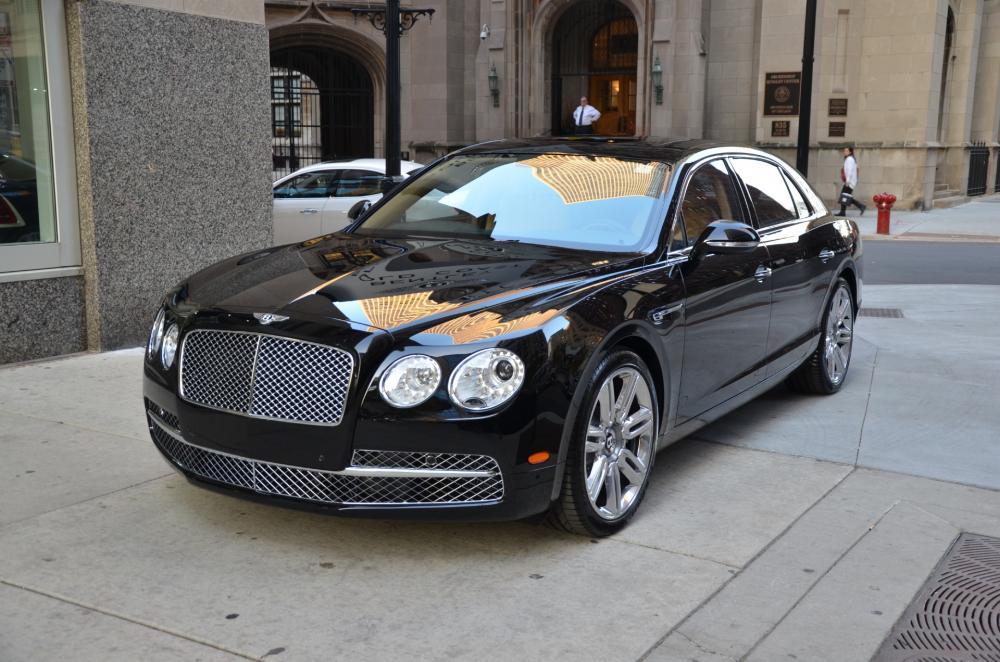gambar menunjukkan sebuah mobil Bentley Flying Spur W12 berwarna hitam sedang diparkir di pinggir jalan