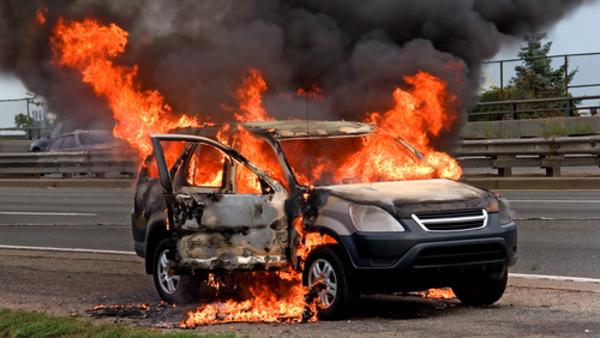 Gambar yang menunjukan mobil yang sedang terbakar di jalanan