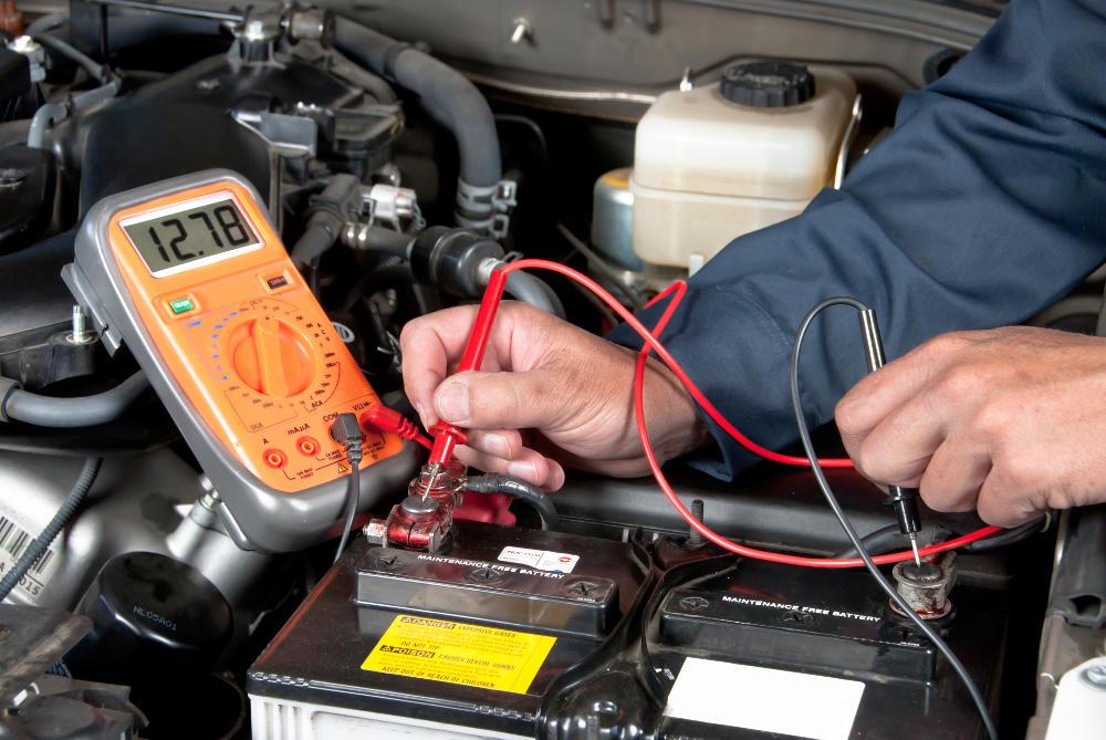 Gambar yang menunjukan seorang mekanik sedang memeriksa baterai mobil
