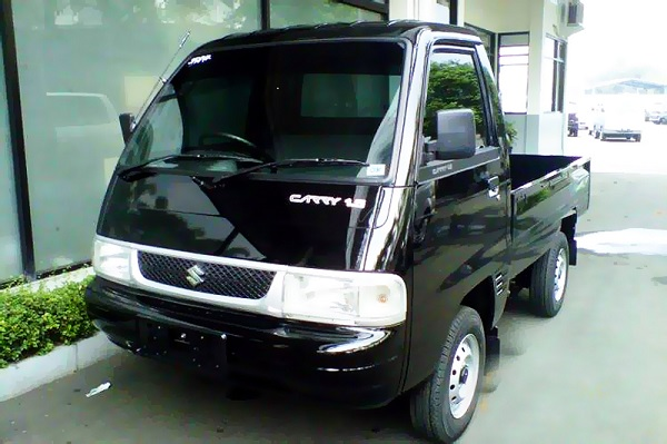 sebuah mobil Suzuki Carry berwarna hitam sedang diparkir di pinggir jalan