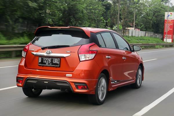 Gambar mobil Toyota Yaris berwarna merah dilihat dari sisi belakang sedang berlaju di jalan