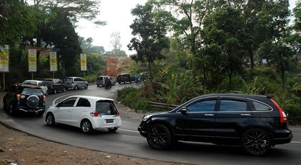 Gambar ini menunjukkan beberapa mobil dengan berbaga warna sedang melewati tikungan