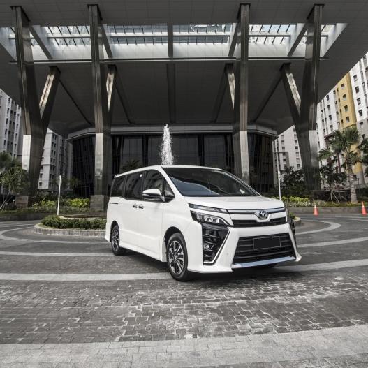 Gambar bagian depan mobil Toyota Voxy berwarna putih sedang parkir di depan gedung kantor
