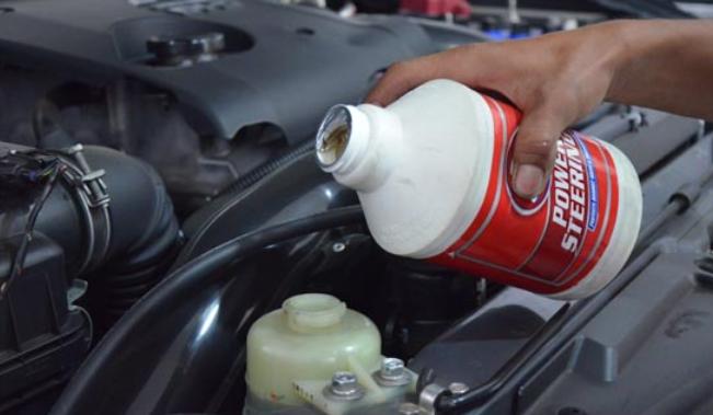 Gambar ini menunjukkan oli power steering sedang dituangkan ke tempatnya pada mobil