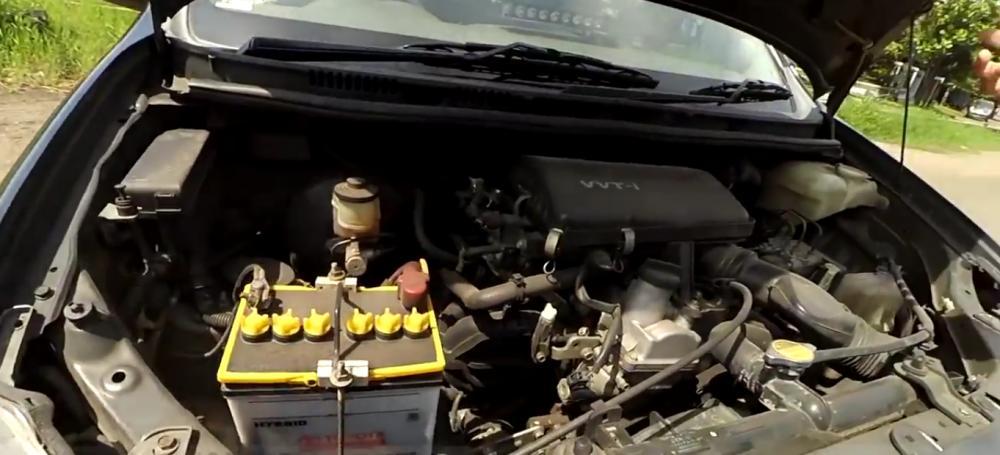 gambar ini menunjukkan mesin mobil Toyota avanza dengan kutub aki berwarna kuning