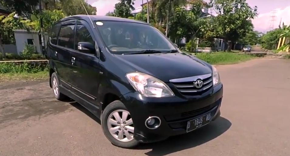 gambar ini menunjukkan Mobil Toyota Avanza warna hitam tampak depan sedang membelok