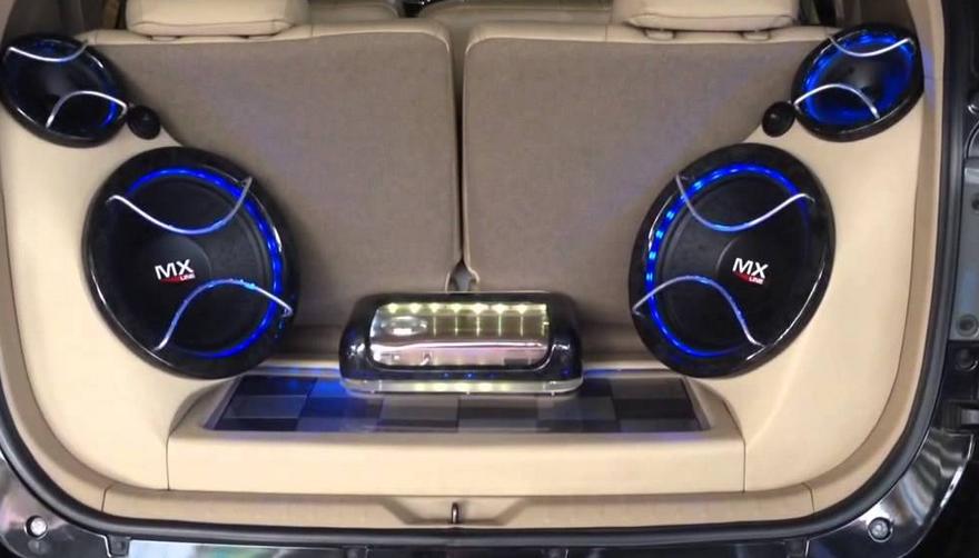 Gambar ini menunjukkan bagasi mobil dengan fitur audio berupa subwoofer warna biru hitam