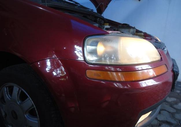 Gambar ini menunjukkan headlamp pada mobilo warna merah dalam keadaan menyala