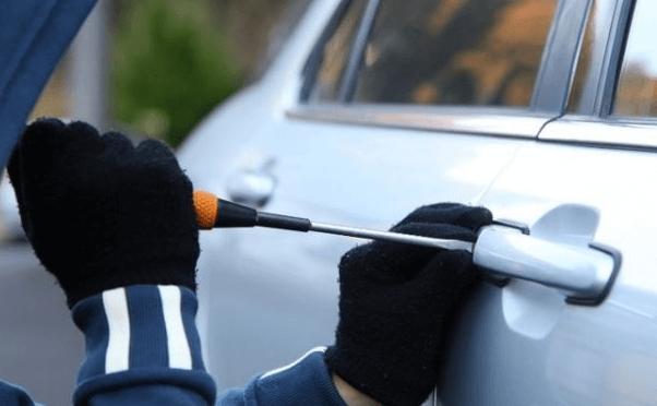 gambar ini menunjukkan sebuah tangan memegang obeng yang di tujukan pada gagang pintu mobil