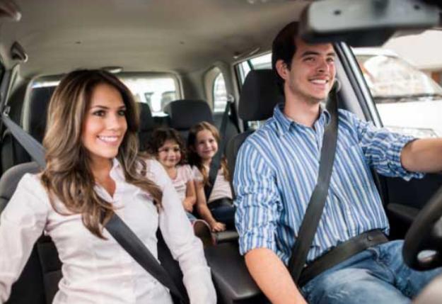 Gambar ini menunjukkan seorang pria sedang mengemudi dan wanita di sampingnya dengan 2 anak di belakangnya dalam mobil