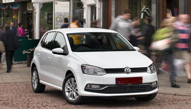 Gambar ini menunjukkan Mobil warna putih tampak depan sedang membelok