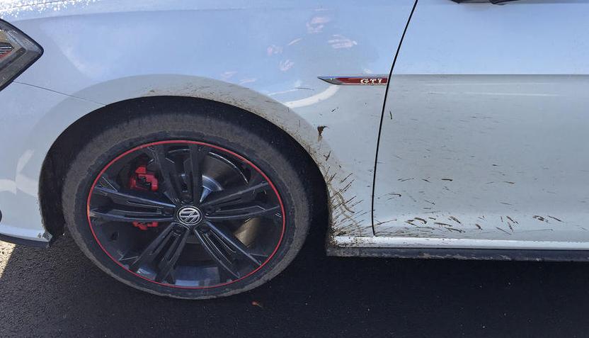 Gambar ini menunjukkan Bodi Mobil warna putih dekat ban Mobil dalam keadaan kotor