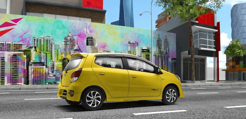 Gambar ini menunjukkan Mobil Toyota Agya warna kuning tampak samping kanan dan sedang berada di jalan