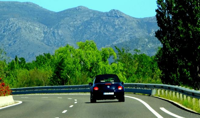 Gambar ini menunjukkan sebuah Mobil warna hitam sedang melaju di jalanan dekat pepohonan