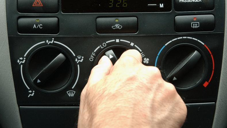 Gambar ini menunjukkan sebuah tangan memegang panel untuk menyalakan dan mematikan ac mobil