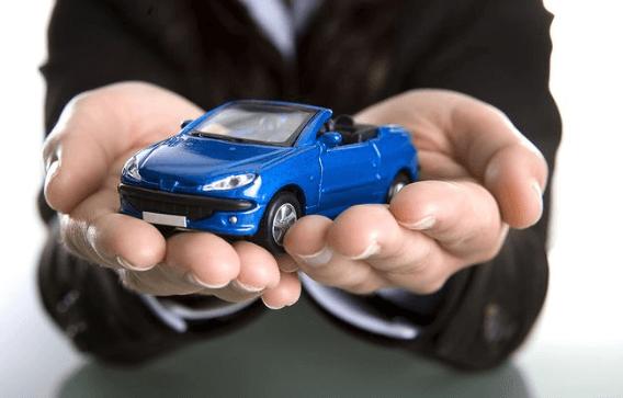 Gambar ini menunjukkan dua buah tangan sedang memegang miniatur Mobil warna biru