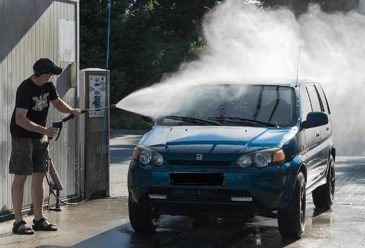Gambar ini menunjukkan seorang pria memegang alat semprot sedang menyemprotkan air pada Mobil
