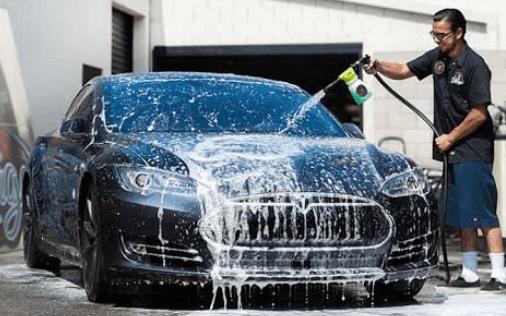 Gambar ini menunjukkan seorang pria menyemprot mobil warna hitam yang berbusa