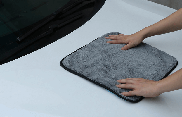 Gambar ini menunjukkan 2 buah tangan memegang lap ditempelkan pada Mobil warna putih