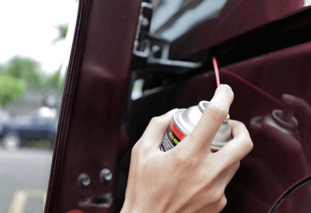 Gambar ini menunjukkan sebuah tangan memegang cairan yang disemprotkan pada mekanisme pintu geser