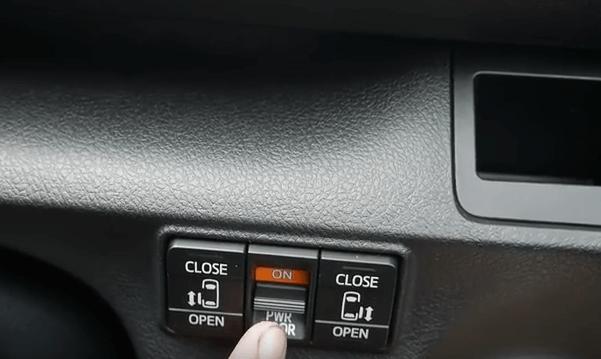 Gambar ini menunjukkan tombol pengatur pintu geser yang berada di bagian dashboard