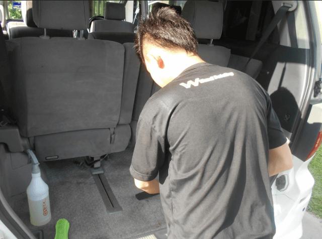 Gambar ini menunjukkan seorang pria seng berada di belakang bagasi Toyota Alphard dengan pintu terbuka