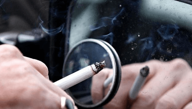 Gambar ini menunjukkan sebuah tangan memegang rokok dan terlihat ada asap di ujungnya