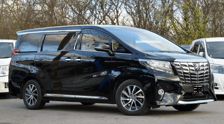 Gambar ini menunjukkan Mobil Toyota Alphard warna hitam tampak depan samping dan terdapat beberapa Mobil di belakangnya