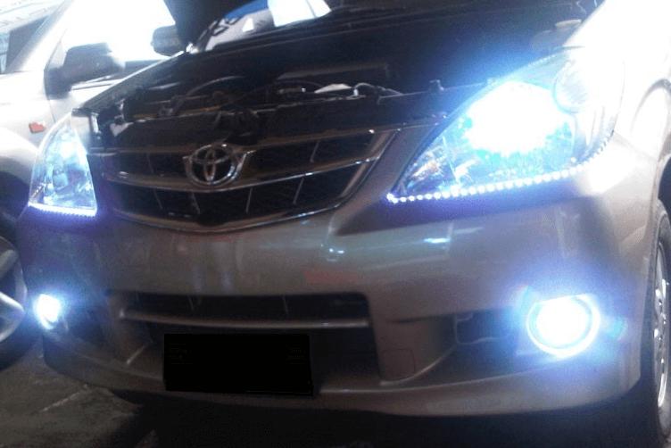 Gambar ini menunjukkan bagian depan Toyota Avanza dalam keadaan lampu foglamp dan headlamp yang menyala