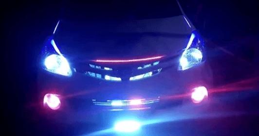 Gambar ini menunjukkan Toyota Avanza yang tidak terlihat jelas dan hanya tampak lampu Mobil yang menyala sangat terang