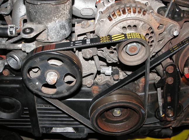 Gambar ini menunjukkan alternator dan belt yang menghubungkan komponen satu dengan lainnya