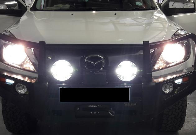 Gambar ini menunjukkan sebuah Mobil tampak depan dengan lampu yang menyala