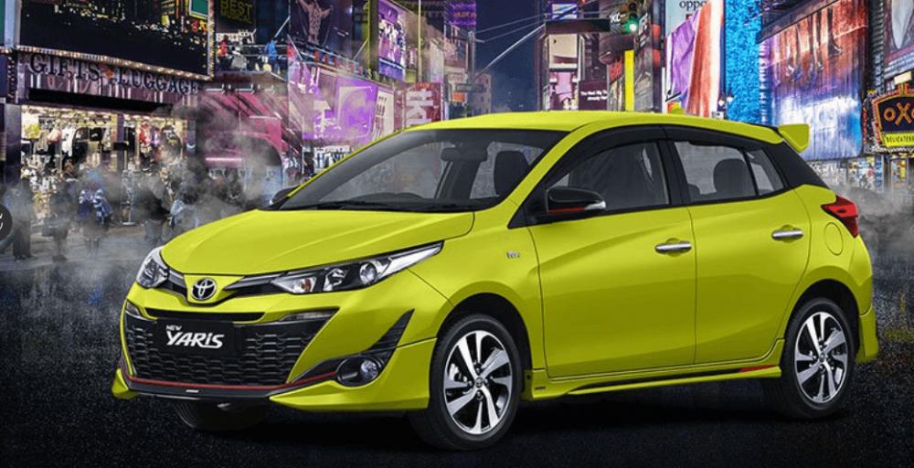 Gambar ini menunjukkan Toyota New Yaris warna kuning tampak samping dan depan