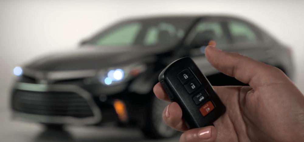 Gambar ini menunjukkan sebuah tangan memegang remot smart key dan terdapat mobil terlihat samar