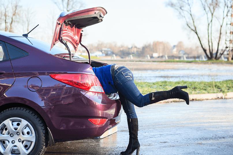 Gambar ini menunjukkan  seseorang masuk bagasi mobil dan terlihat kakinya saja