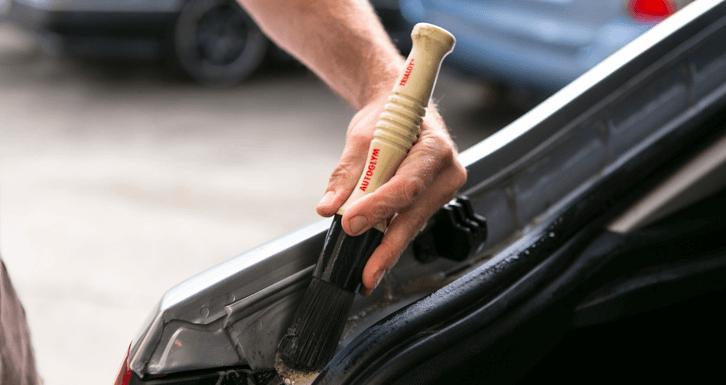 Gambar ini menunjukkan sebuah tangan memegang kuas sedang membersihkan sela-sela pada bagasi Mobil