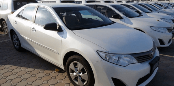 Gambar ini menunjukkan Mobil warna purih yang sedang parkir berjejer
