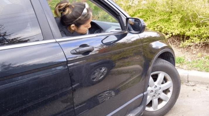 Gambar ini menunjukkan seorang pengemudi wanita sedang melihat keluar dari jendela Mobilnya