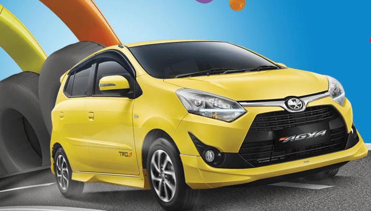 Gambar ini menunjukkan Mobil Toyota Agya warna kuning tampak depan dan samping kanan