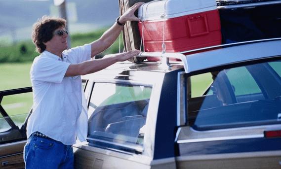 Gambar ini menunjukkan seorang pria sedang memegang roof rack pada Mobil