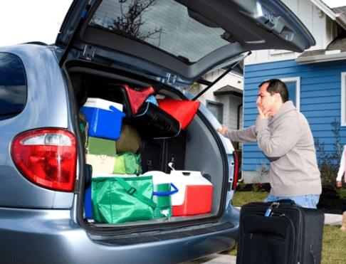 Gambar ini menunjukkan seorang pria sedang menata barang di bagasi Mobil sampai penuh