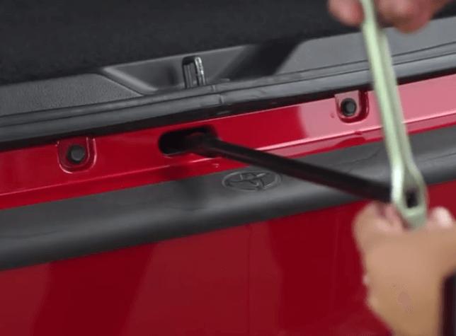 Gambar ini menunjukkan sebuah tangan memegang alat yang dimasukkan ke dalam lubang bawah bagasi untuk menurunkan ban serep