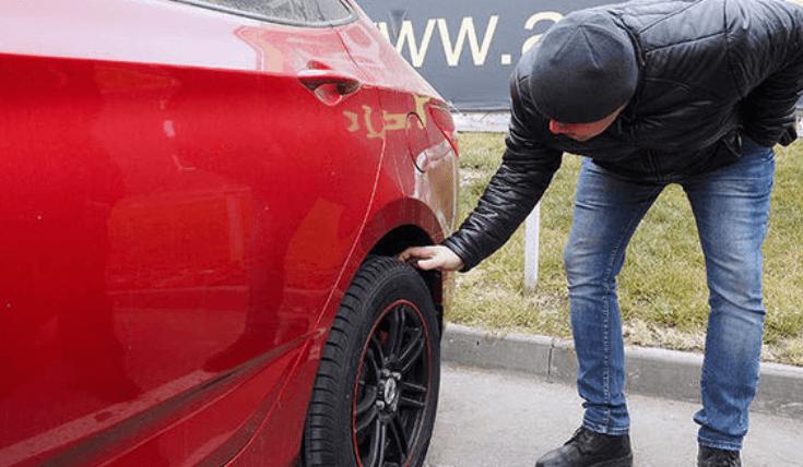 Gambar ini menunjukkan seorang pria sedang menyentuh ban mobil dengan bodi warna merah