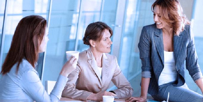 Gambar ini menunjukkan 3 orang wanita sedang melakukan pembicaraan dan yang satu duduk di atas meja