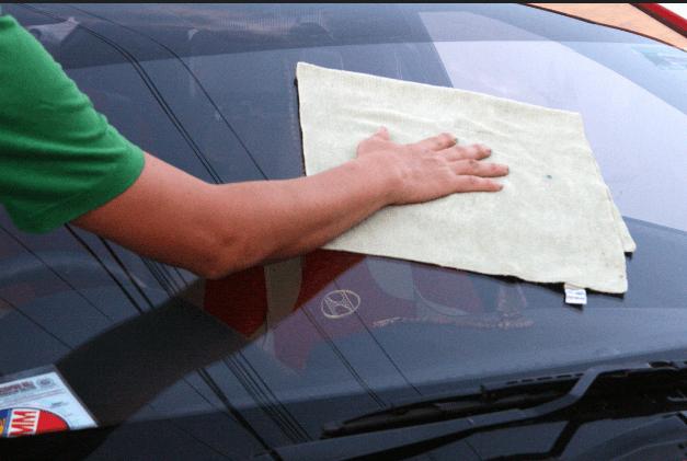 Gambar ini menunjukkan sebuah tangan memegang kanebo untuk mengelap kaca luar Mobil